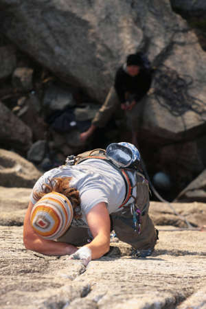 A female climber reaches for a higher hold. photo