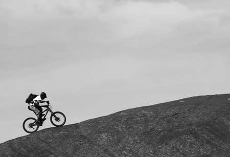 A lone mountainbiker rides a steep section of Moad's famous slickrock mountain bike trail.
