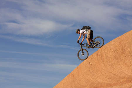 fearless: A fearless mountain biker drops down a steep section of Moabs slickrock trail. Stock Photo