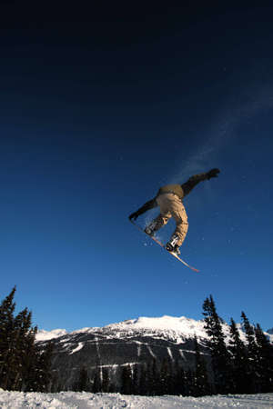 A snowboarder in flight on Whistler Mountain, BC.