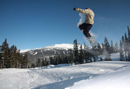 A snowboarder flies through the air in Whistler, BC.
