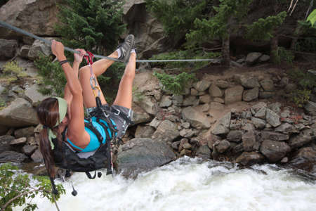 A beautiful girl crosses a river via a tyrolean traverse. Stok Fotoğraf