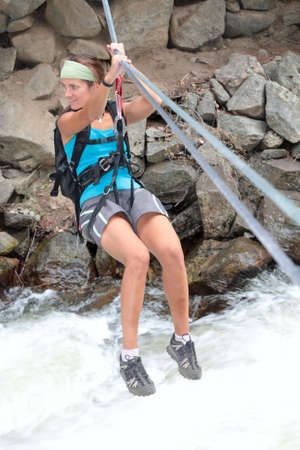 thrilling: A girl crosses a raging river via a tyrolean traverse. Stock Photo