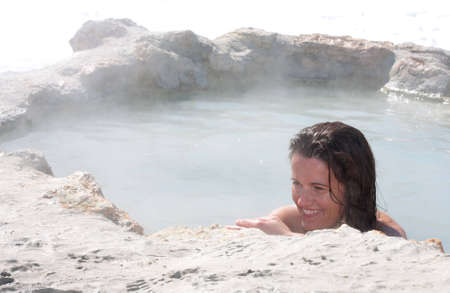 A woman has a relaxing soak in a natural hot spring in central california. Stock Photo