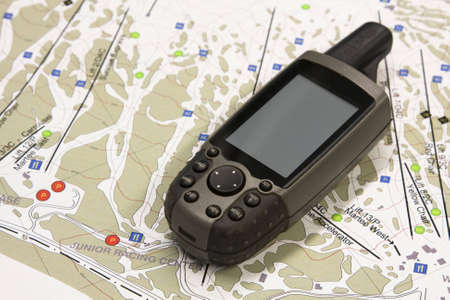 A handheld global positioning unit sits on a topo map.  The screen is blank and ready for your text. photo