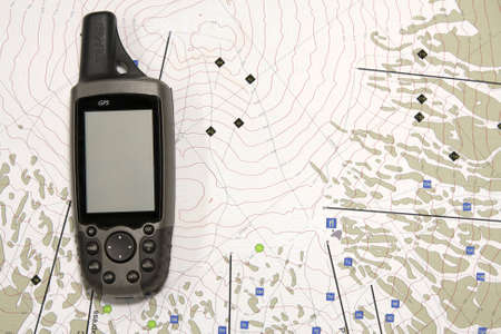A handheld GPS unit sits on a topographical map.  The blank screen is ready for your text. photo