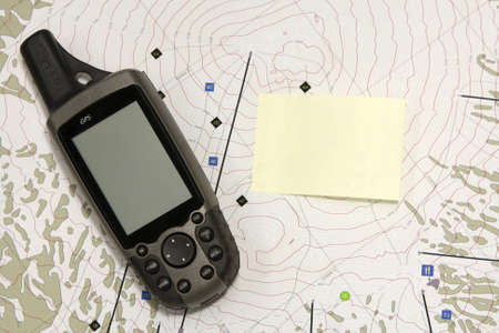 A hand held GPS device sits on a topo map.  The blank screen and a blank yellow sticky note are ready for your text. photo