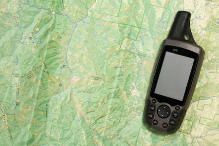 A handheld GPS unit sits on a topo map.  The blank screen is ready for your text. Stok Fotoğraf
