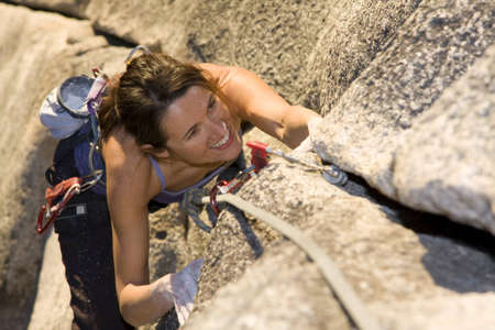 A fit and attractive girl climbs a granite rock in Squamish British Columbia Canada.