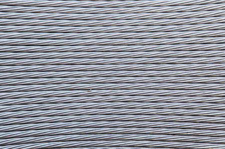 Coils of braided steel cable with a diagonal shadow. photo
