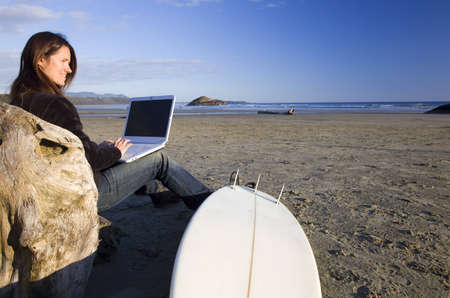 laptop: A woman works wirelessly on her computer at the beach. Stock Photo