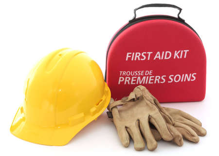 A first-aid kit, hardhat, and gloves spell out the need for safety in the workplace. Stok Fotoğraf