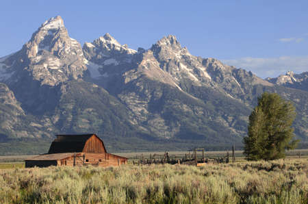 A weathered barn sits against the backdrop of the Grand Tetons in Wyoming, USA Stock fotó