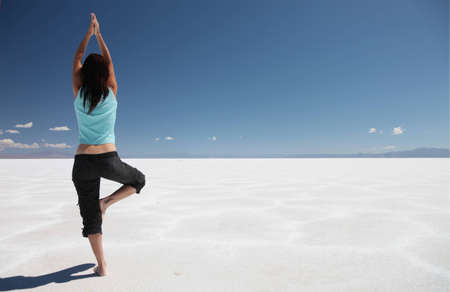 A woman practising yoga on the Salinas Grandes in northern Argentina. Stok Fotoğraf