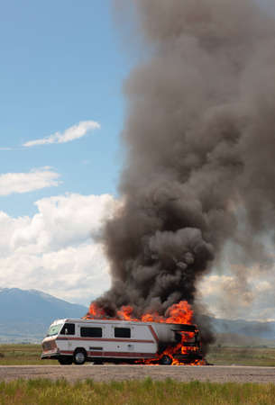 An RV is engulfed in flames at the side of a highway on a hot summers day.  So much for the vacation...