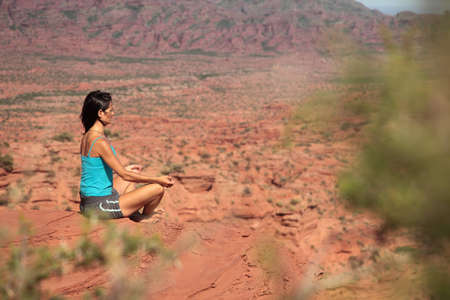A young woman meditates in a desert in Argentina.