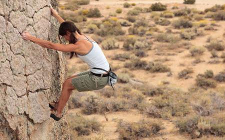 ascends: A strong female climber ascends a rock face near Bishop California.