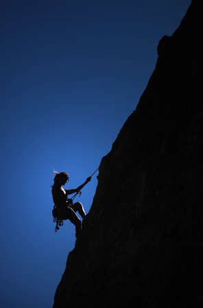 A climber hangs from a thread on the side of a cliff. Zdjęcie Seryjne