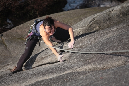 steep cliff: A strong woman struggles up a steep rock face in Squamish British Columbia Canada. Stock Photo