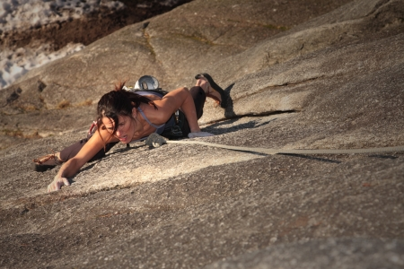 steep cliffs: A strong woman struggles up a steep rock face in Squamish British Columbia Canada. Stock Photo
