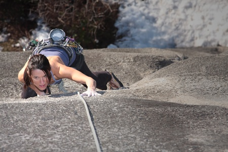 A strong woman struggles up a steep rock face in Squamish British Columbia Canada. Stock Photo