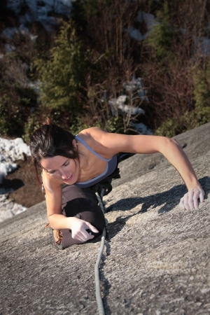 rock climb: A strong woman struggles up a steep rock face in Squamish British Columbia Canada