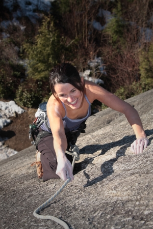A strong woman struggles up a steep rock face in Squamish British Columbia Canada  photo