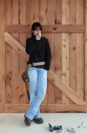 A carpenter stands in front of a wooden door she has just finished building  photo