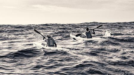 Een paar surfski-roeiers begeleiden hun oceaankajaks in ruwe golven dichtbij Houtbaai, Zuid-Afrika