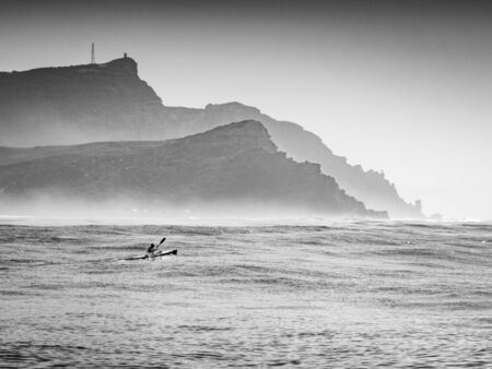 An Ocean Kayak racer paddles his surfski towards Cape Point in the early morning Stock Photo