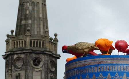 Mysterious sculpture of colorful pigeons watching from the top of a column near a cathedral