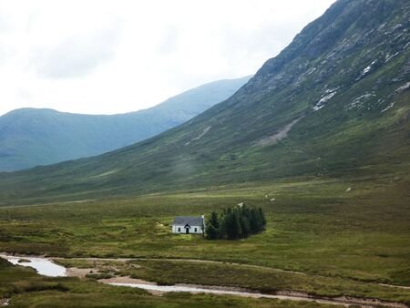 Lonely house on the plain of a valley next to a river in the highlands