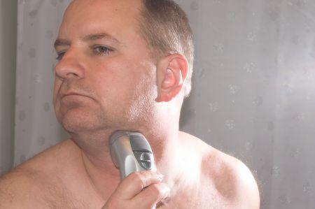 hombre afeitandose: Hombre que afeita en luz de la ventana