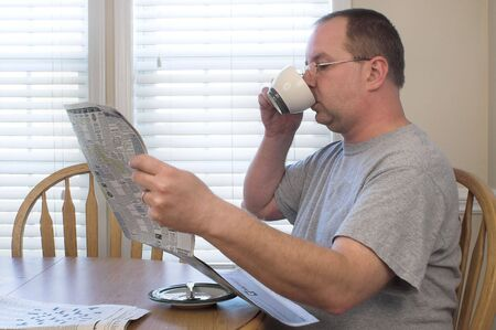 hombre tomando cafe: Caf� que bebe del hombre y lectura de un peri�dico