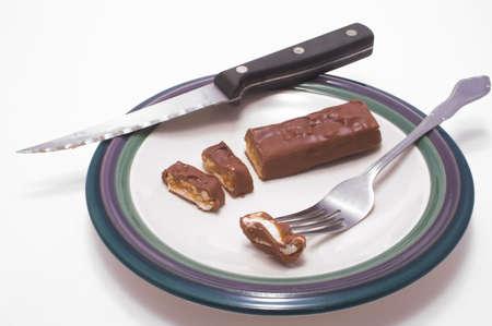candy bar: Una barra de chocolate dulce ser cortado en rodajas en un plato. Foto de archivo