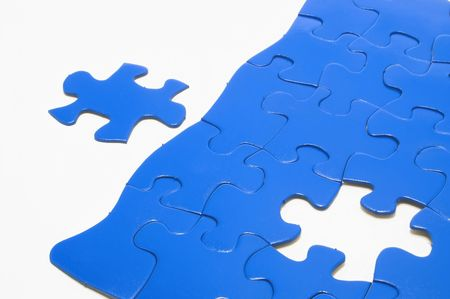 A close-up of a jigsaw puzzle with a missing puzzle piece. photo