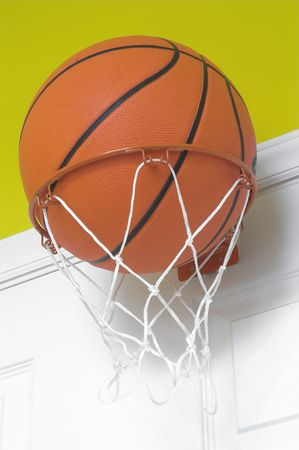 b ball: A basketball in a small indoor basketball goal.