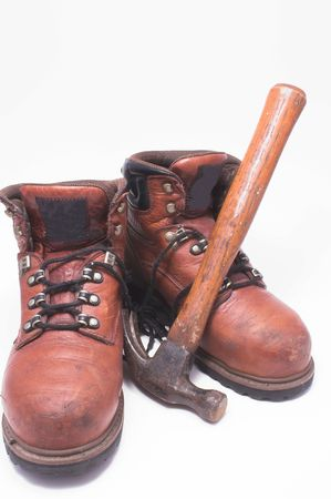 claw hammer: A pair of steel toed work boots and a claw hammer. Stock Photo