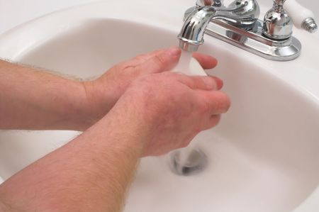 antibacterial soap: A person washing their hands with soap and water.