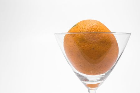 martini glass: A fresh orange in a martini glass.