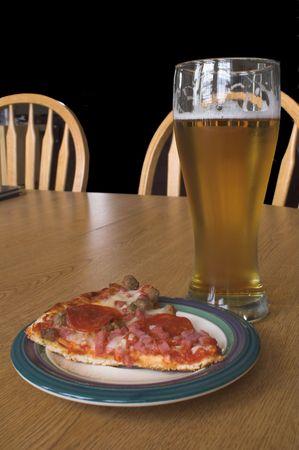 pilsner: Una rebanada de pizza y una cerveza en un vaso Pilsner.