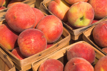 Delicious peaches on display at a farmers market. Stock Photo