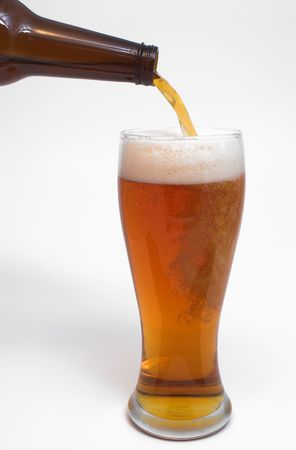 near beer: A golden colored beer being poured into a pilsner glass.