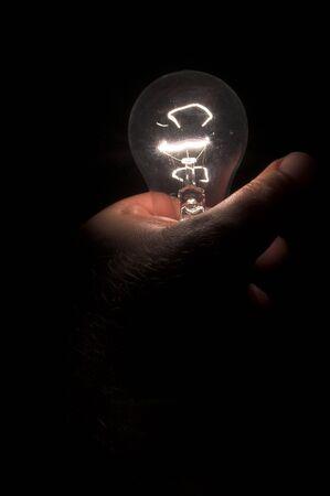 enchufe de luz: Una persona de encender una bombilla mediante la celebraci�n de la misma.