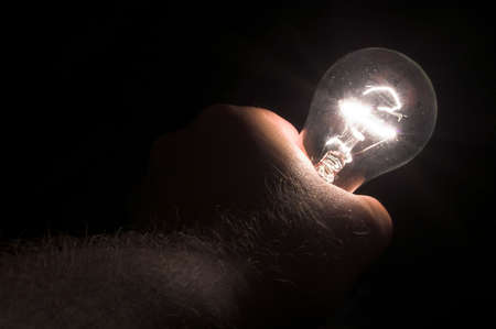 A person powering a light bulb by holding it. Stock Photo - 981063