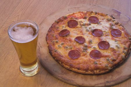 near beer: A slice of pizza and a beer in a pilsner glass. Stock Photo
