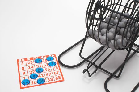 A bingo cage, balls with numbers, card and markers. photo