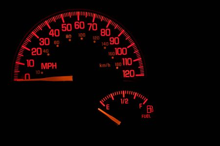 gas gauge: A red speedometer and gas gauge on an automobile dashboard. Stock Photo