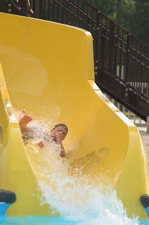 A young boy sliding down a water slide. photo