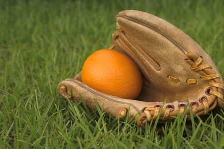 gant de baseball: Un d�licieux orange dans un gant de baseball. Banque d'images